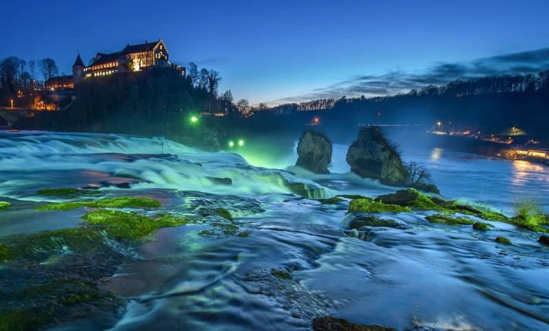 Rhine Falls is illuminated at night